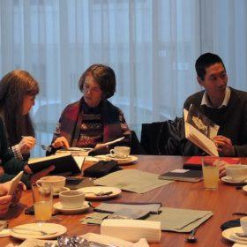 Gruppe Zeichner an großem Tisch beim BEtrachten von Skizzenbüchern