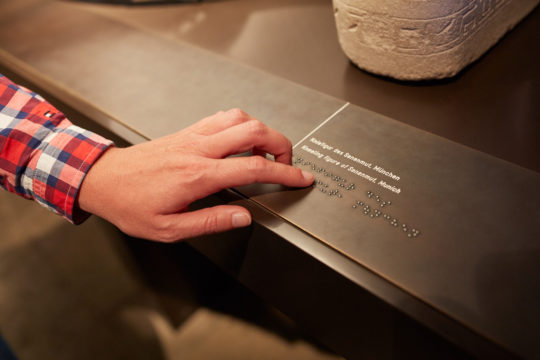 Hand auf Brailleschrift