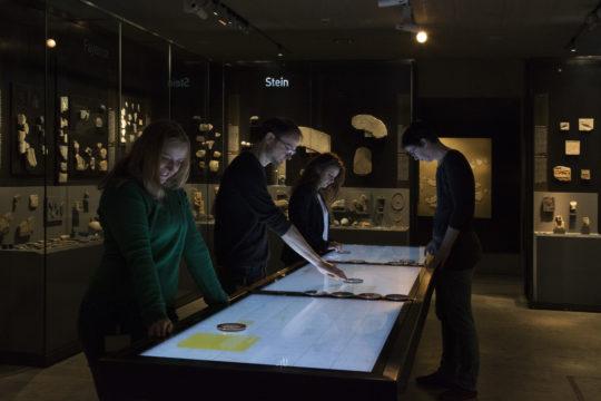 Menschen an einer Medienstation im Museum