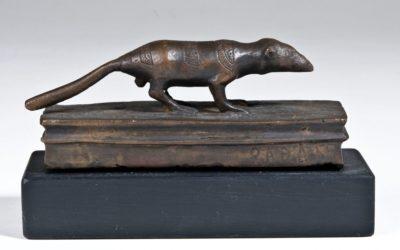Eine nach rechts gewandte, stehende Spitzmaus aus Bronze mit ausgestrecktem Schwanz, unter ihr ein Bronzeblock.