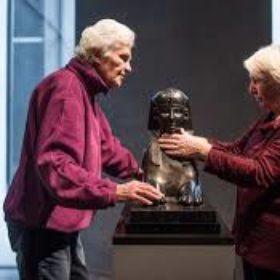 Zwei Frauen betasten eine Statue