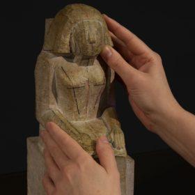 Zwei Hände betasten die Nachbildung einer ägyptischen Statue