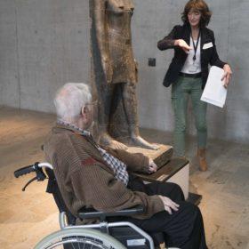 Mann im Rollstuhl vor einer ägyptischen Statue