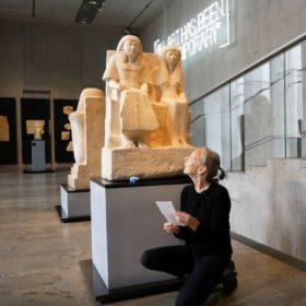 Künstlerin Ruth Geiersberger knieend vor einer altägyptschen Statue
