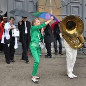 Ruth Geiersberger in grünem Anzug neben einem Tuba-Spieler