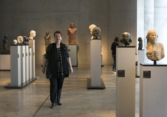 Dr. Sylvia Schoske steht inmitten von altägyptischen Skulpturen im Museum