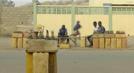 Auf einer staubigen Straße vor einer hellgelben Mauer sitzen drei junge Schwarze Männer auf Holzbänken. Vor Ihnen stehen gelbe Plastiktanks, auf denen sich Holzkästen voller Flaschen befinden.