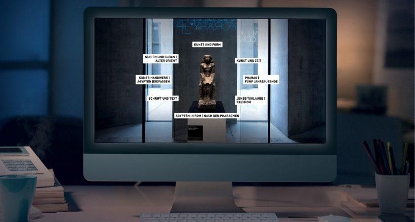 Ein Computerbildschirm steht in einem dunklen Raum, auf dem Bildschirm ist die Startseite der Grand Tour, der digitalen Ausstellung, angezeigt