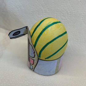 Auf einem weißen Hintergrund ein gelb-bkau gestreift bemaltes Osterei, das in einer gebastelten Krone sitzt.