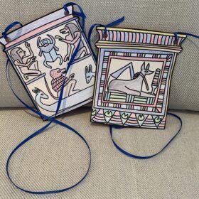 Zwei mit Buntstifte ausgemalte Bilder von Pektorale, ausgeschnitten und mit Bänder versehen. Einer zeigt ein Pavian in einem Schiff, darüber ein Skarabäus. Der zweite zeigt einen liegenden Schakal.